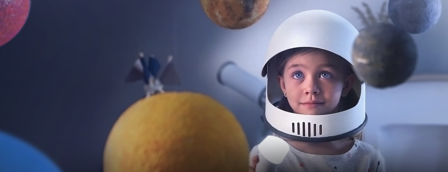 An illustrative image of a child wearing a helmet looking at a floating planet