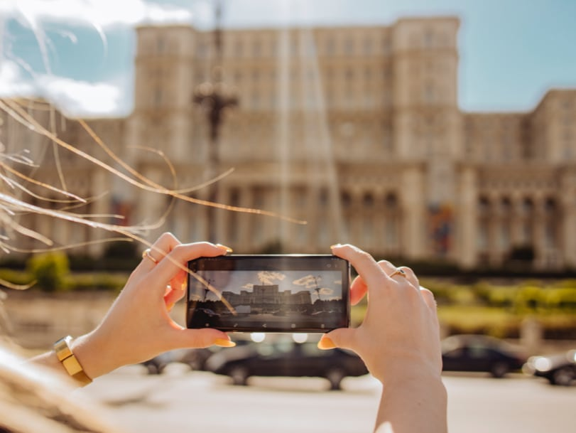 Girl taking pictures of Palace of Parlament in Bucharest with Samsung phone representing Shot Suggestion Mode and Ultra- wide angle lens.