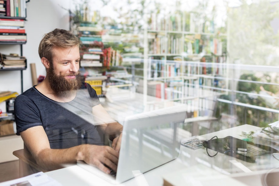 A double-exposure shot of a man sitting at a desk on his laptop, there is a book shelf in the background