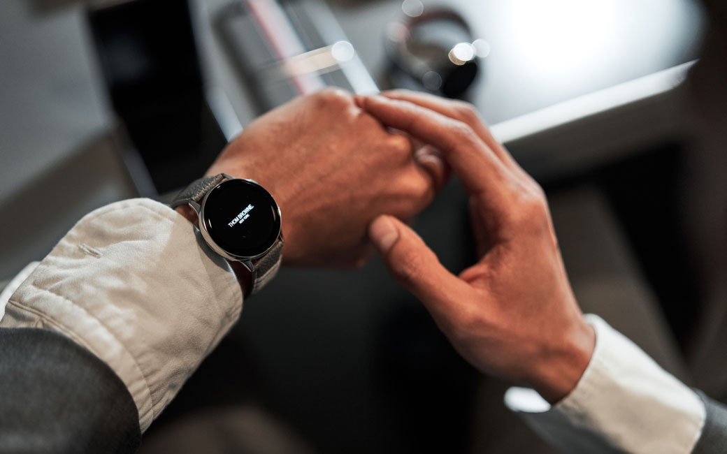 A closeup of a man's wrist wearing a grey Galaxy Watch Active2 Thom Browne Edition with the rest of the set featured in the background off-focus.