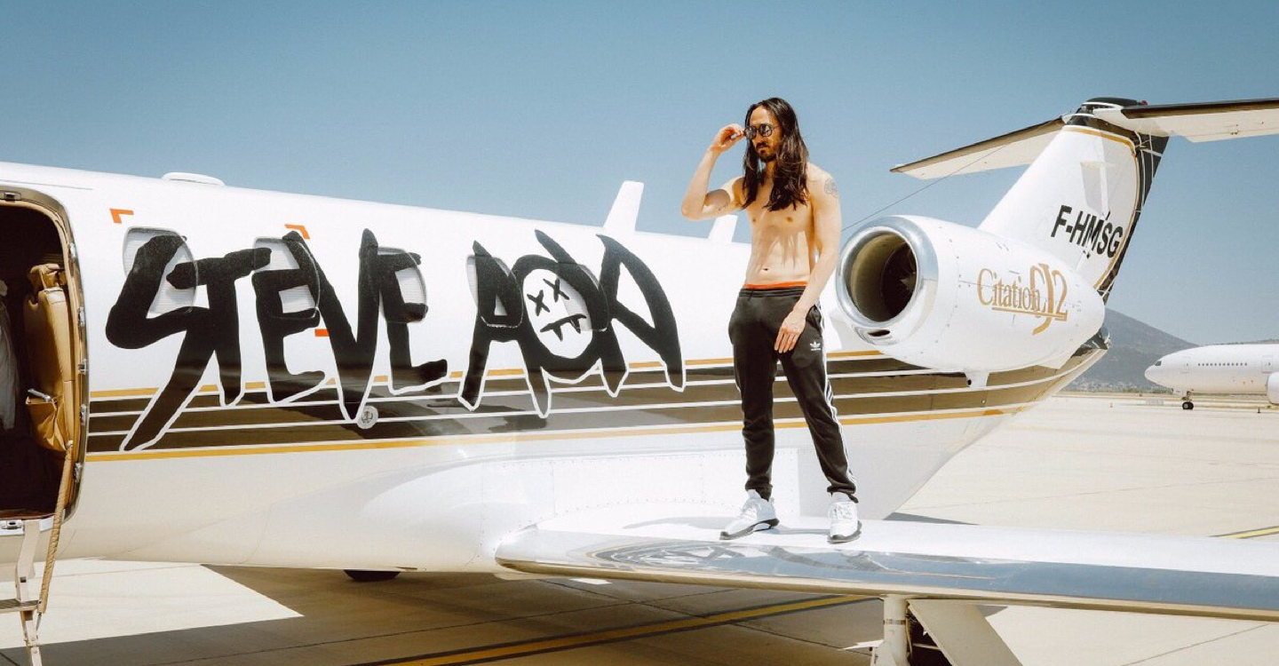 A full-frontal photo of Steve Aoki standing topless on top of the wing of his white private jet as he puts on his aviator sunglasses