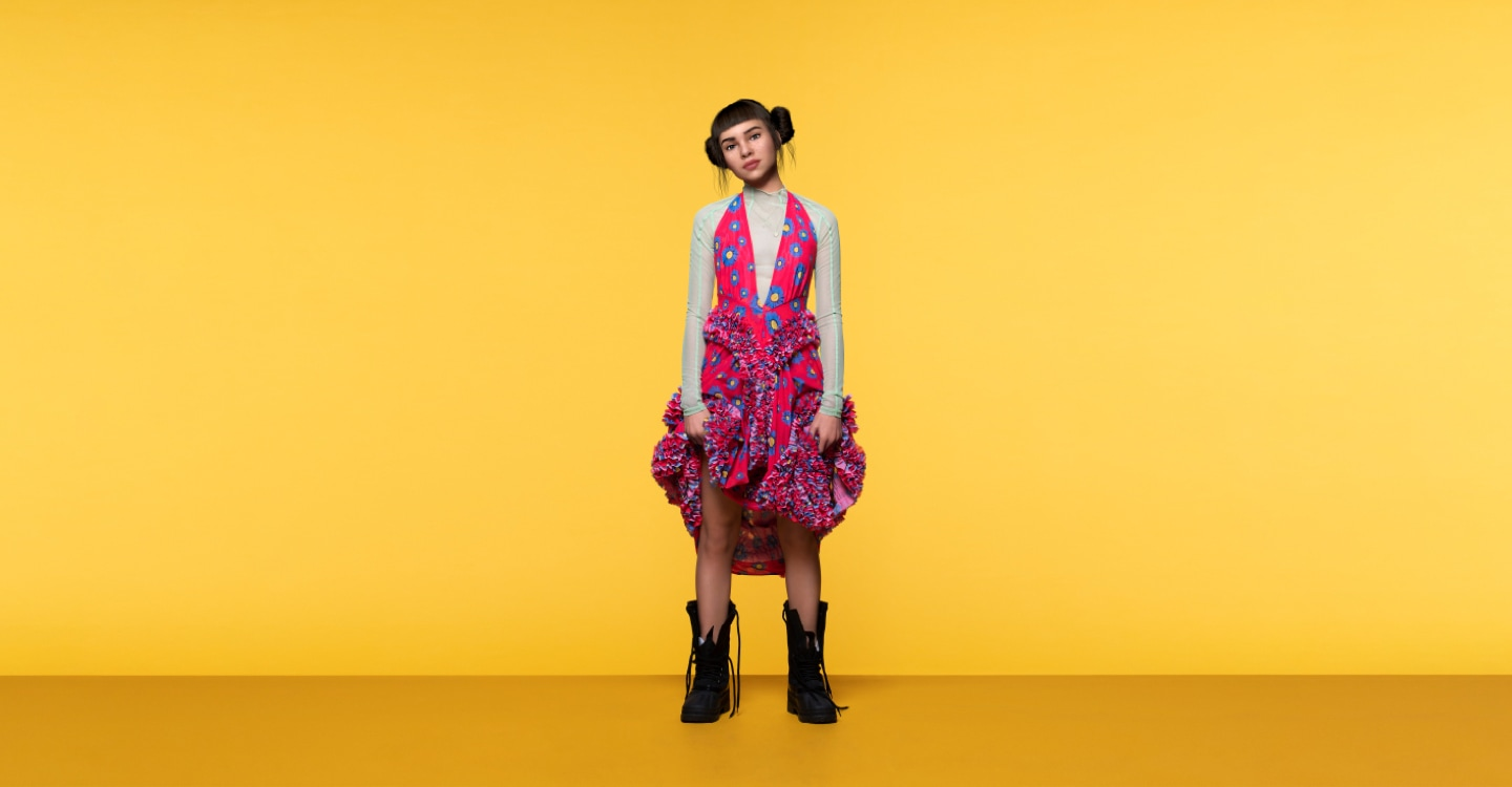 A full-body, promotional shot of Lil Miquela wearing a brightly coloured dress while looking confidently into the camera
