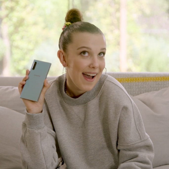 Millie Bobby Brown, sentada en un sofá, sostiene un Galaxy Note10 en color Aura Glow