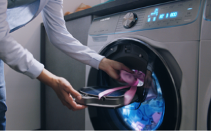 Laundry being inserted into the Samsung QuickDrive washing and dryer machine using the AddWash feature