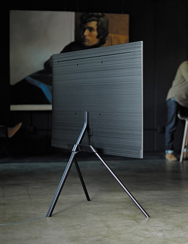 A lifestyle image of the 2018 new QLED TV Q7F.  Image shows QLED TV put on the floor facing back, with its Studio Stand option.