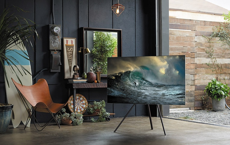 A lifestyle image of the 2018 new QLED TV Q7F.  Image shows QLED TV put on the floor with its Studio Stand option in the middle of the place.