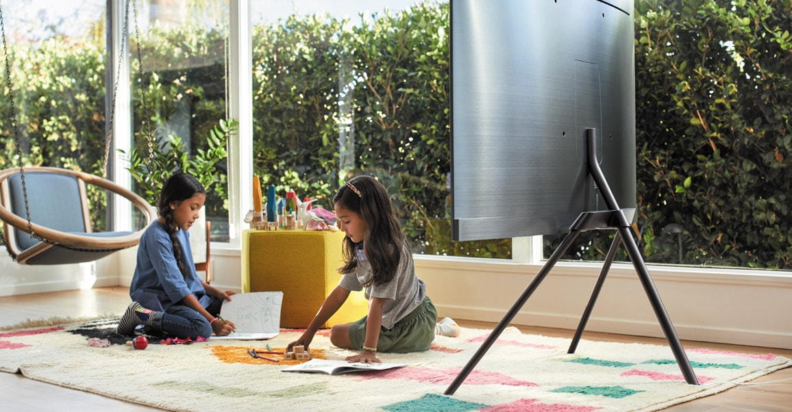 A lifestyle image of the 2018 new QLED TV Q8C.  QLED TV is put on a floor with its Studio Stand and children is playing besides it.