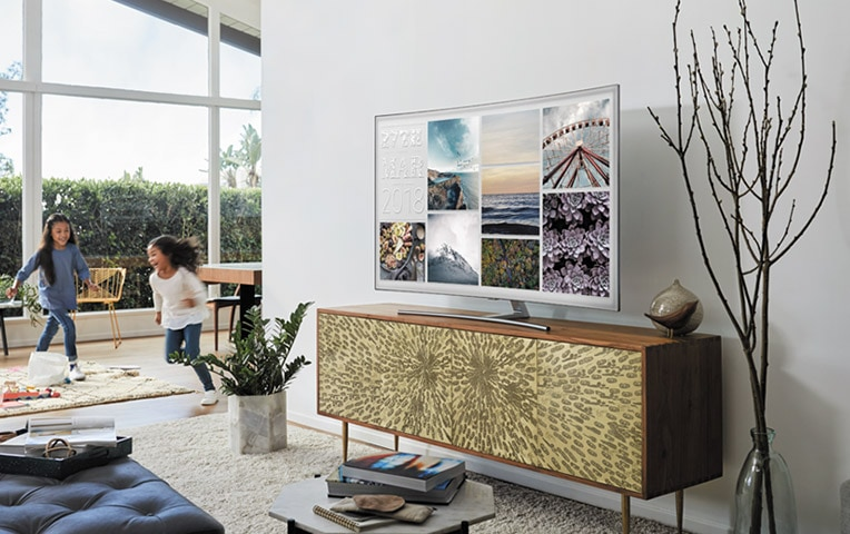 A lifestyle image of the 2018 new QLED TV Q8C.  QLED TV is put on a table with its photo mode on and children is playing in the living room.