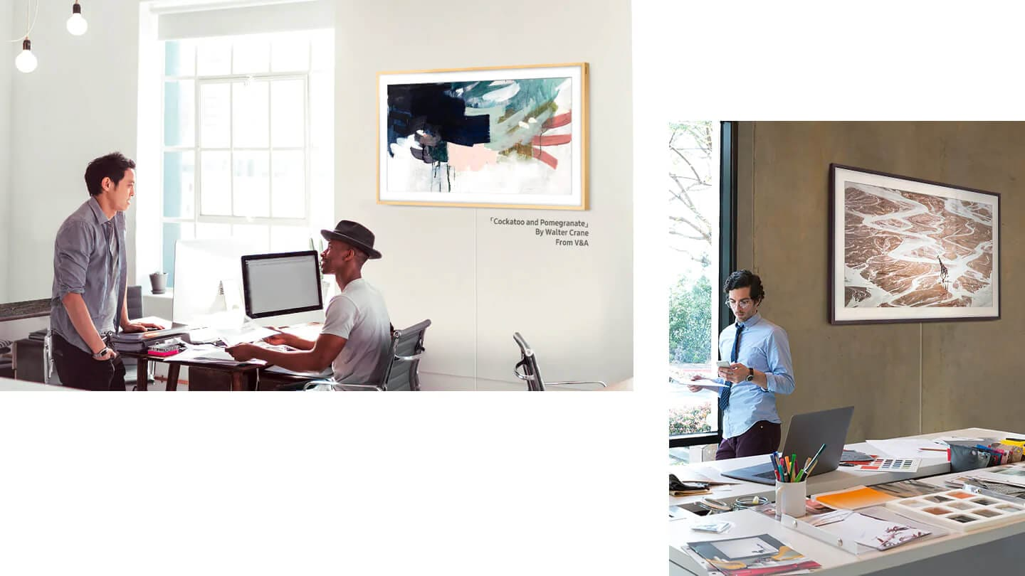 "Two men talk in an office where The Frame hangs on the wall displaying ""Cockatoo and Pomegranate"" by Walter Crane. In another office, a man leans against a large window holding a document and a mobile phone. The Frame shows a photo of a giraffe in the wild."