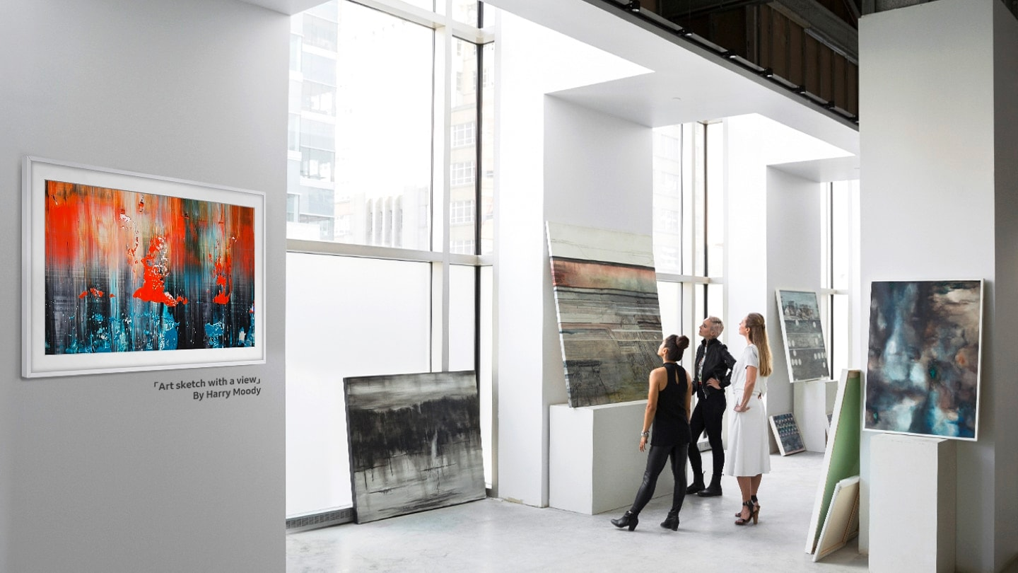 "The Frame with a white bezel is hanging on the wall of a gallery. It's displaying ""Art sketch with a view"" by Harry Moody. Other modern art pieces are displayed nearby and 3 women are looking intently at one of the pieces."