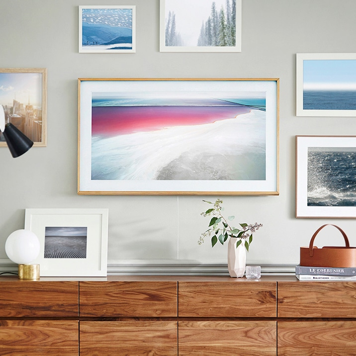 Samsung's The Frame hanging on the wall with other picture frames