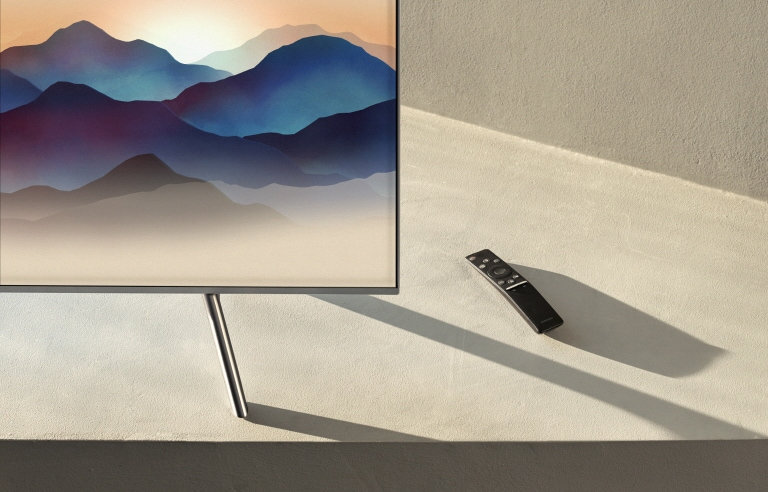 Samsung's One remote control and QLED TV displaying a mountain content by it's Ambient mode décor.