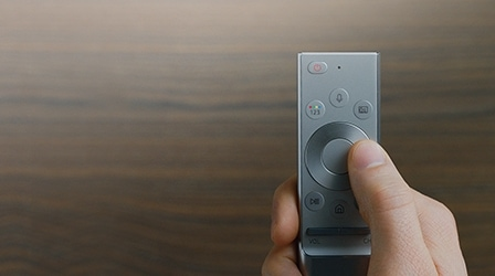 A shape of One Remote Control with a thumb clicking the remote's button.