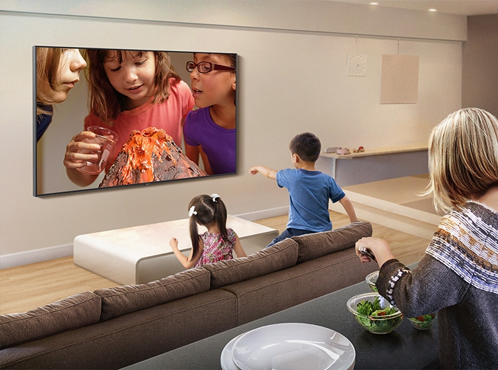 Children are watching kids' science experiment video in the living room, and behind them, their mother is serving a salad at the island table. The experiment video is being streamed through YouTube app on Samsung Smart TV.