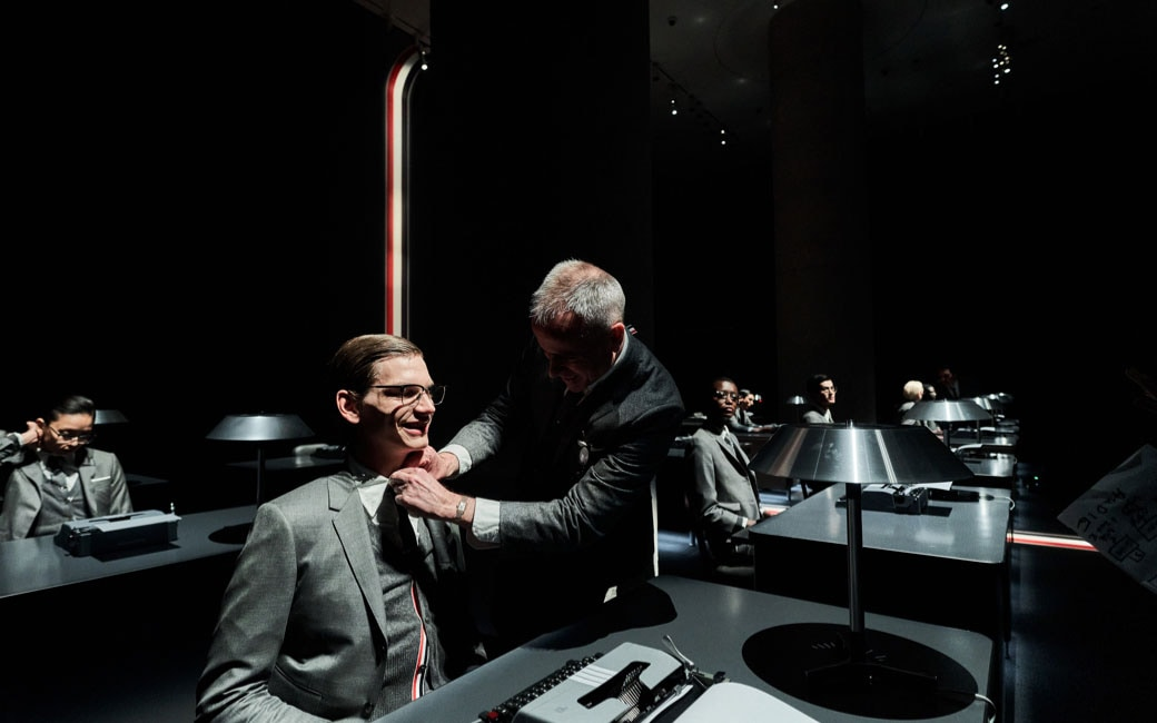 Designer Thom Browne fixes a model's tie during the dress rehearsal as he hovers over him. In the background, you can see the other models at their desks in office uniform.
