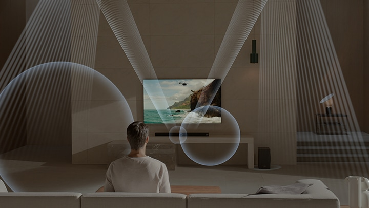 TV being turned on in a living room, while one person sitting on a sofa across from it views the TV. A soundwave graphic displays how Samsung soundbar delivers better sound quality in your room through waves sent out.