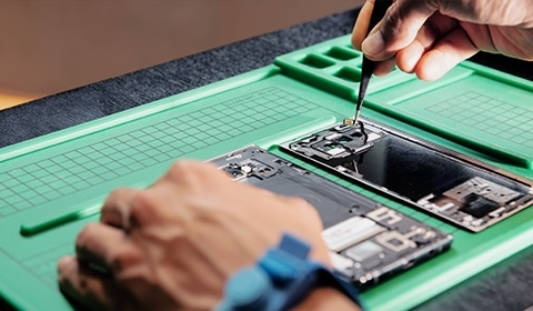 Closeup of the hands of a technician repairing a phone on a table. The phone has been taken apart with the interior components exposed