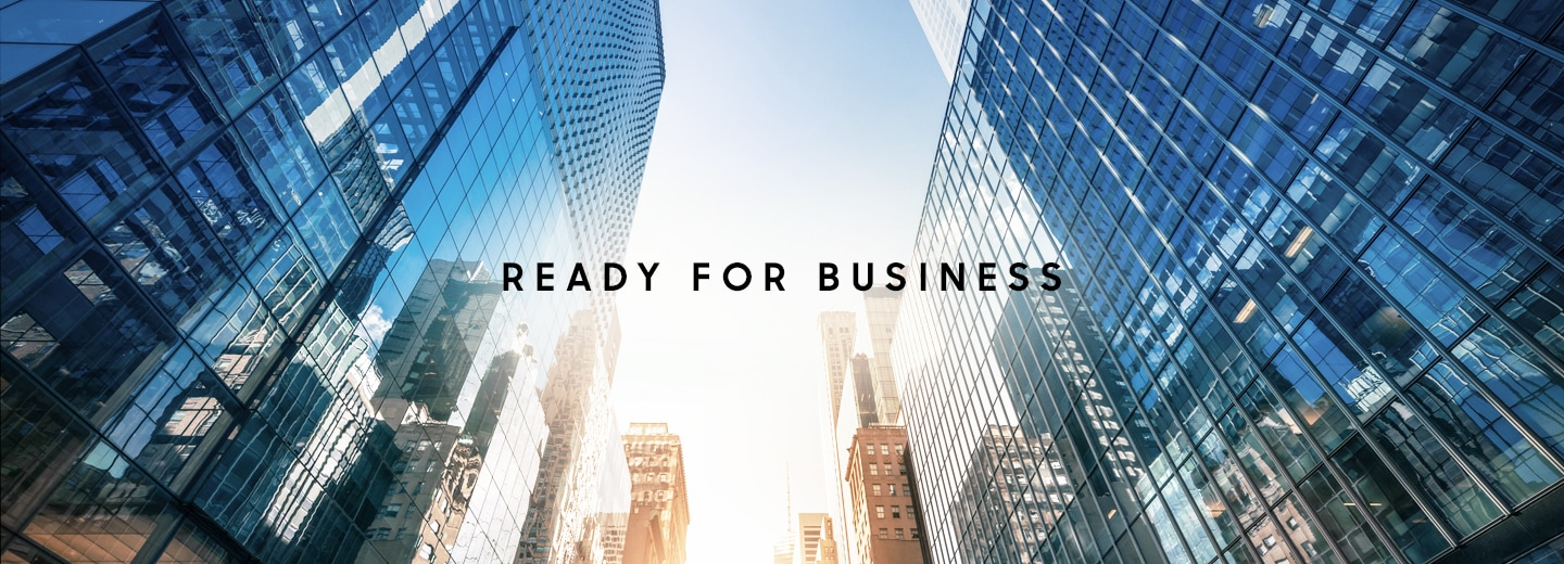 A skyward facing photo between multiple glass skyscrapers with text overlaid that says Ready for business