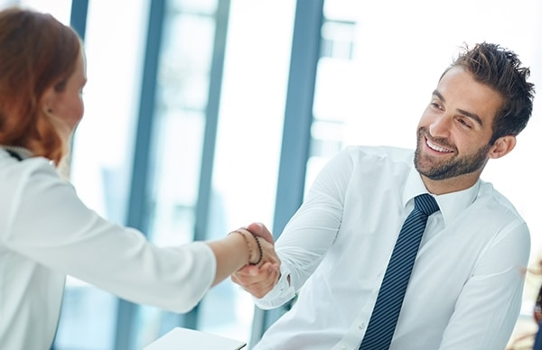 An image showing two smiling office workers shaking hands