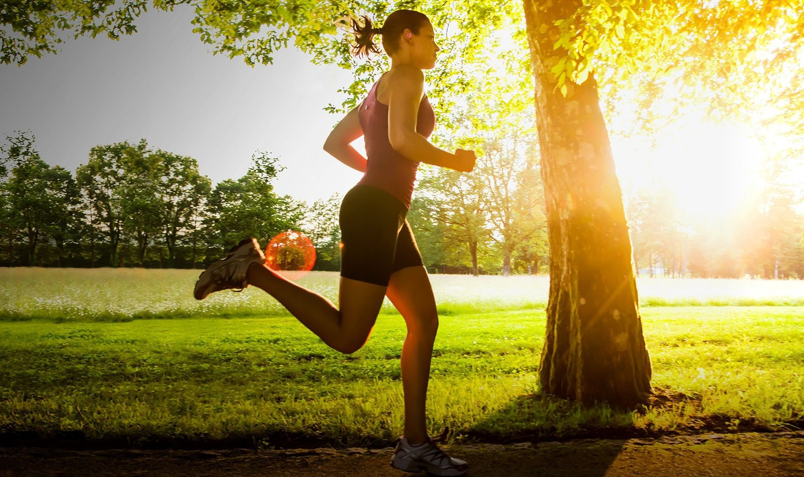 Background image of woman running in a park wearing Gear IconX