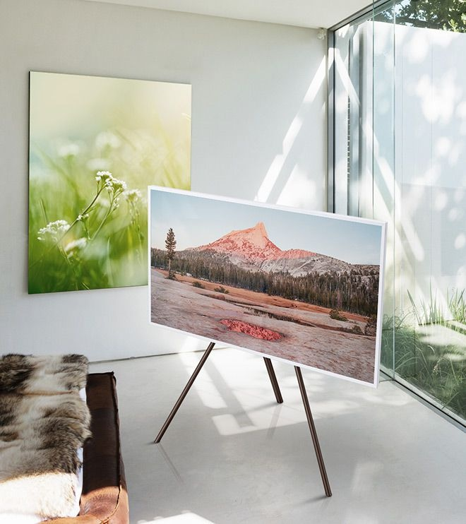 The Frame displaying a photo with no matte in the corner of a room away from the wall and window and placed on a white studio stand.