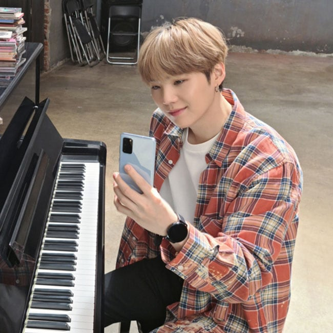 SUGA from BTS sitting in front of a piano, he is holding out a Galaxy S20 and smiling as though he is speaking to someone via video chat/livestreaming