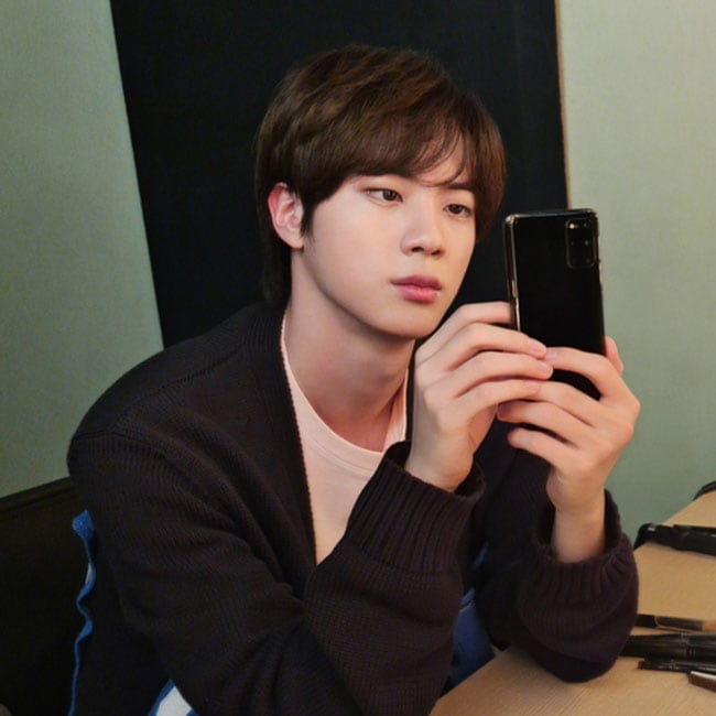 Jin from BTS sitting in a dressing room, he has his elbows on the dressing table and is playing with a Galaxy S20