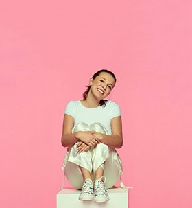 A studio PR photo portrait of Millie Bobby Brown against a pink backdrop. She's smiling with her head leaned to the side and sitting on a white box with her hand laid over the other holding her legs.