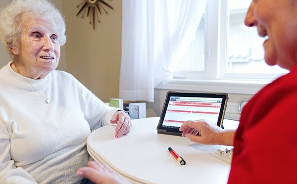 An image showing an elderly lady talking to a health consultant about materials shown on the screen of a tablet.