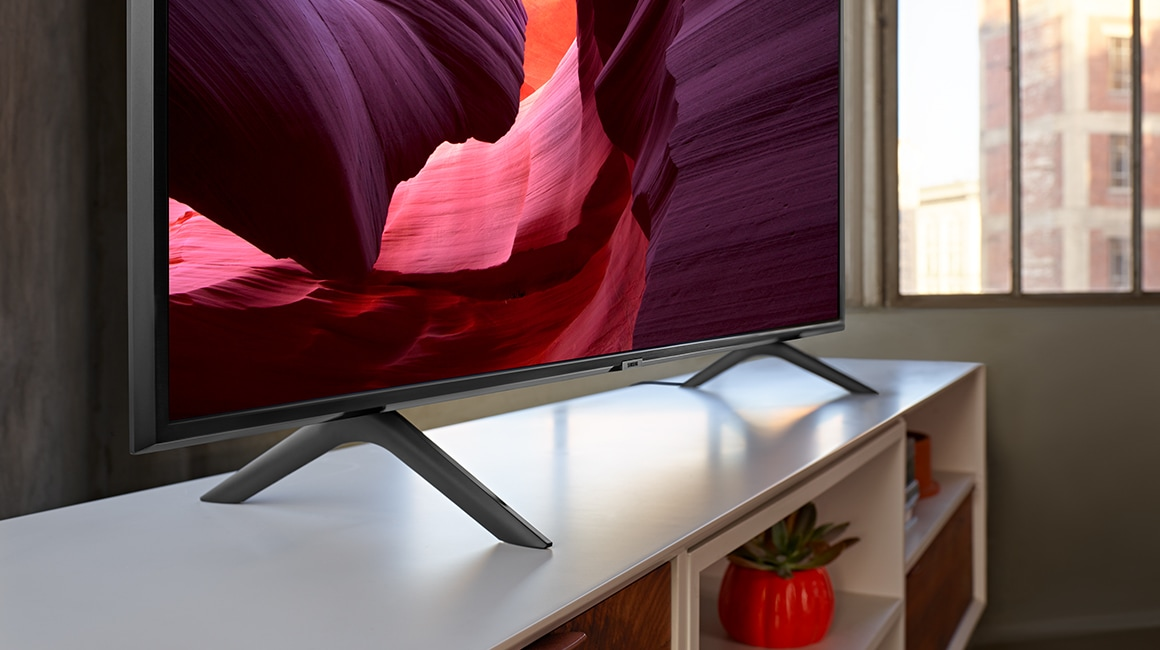 A Close up shot of stand design of the 2019 new Samsung QLED Q60R. Image shows the sleek design of Q60R put on the TV table.