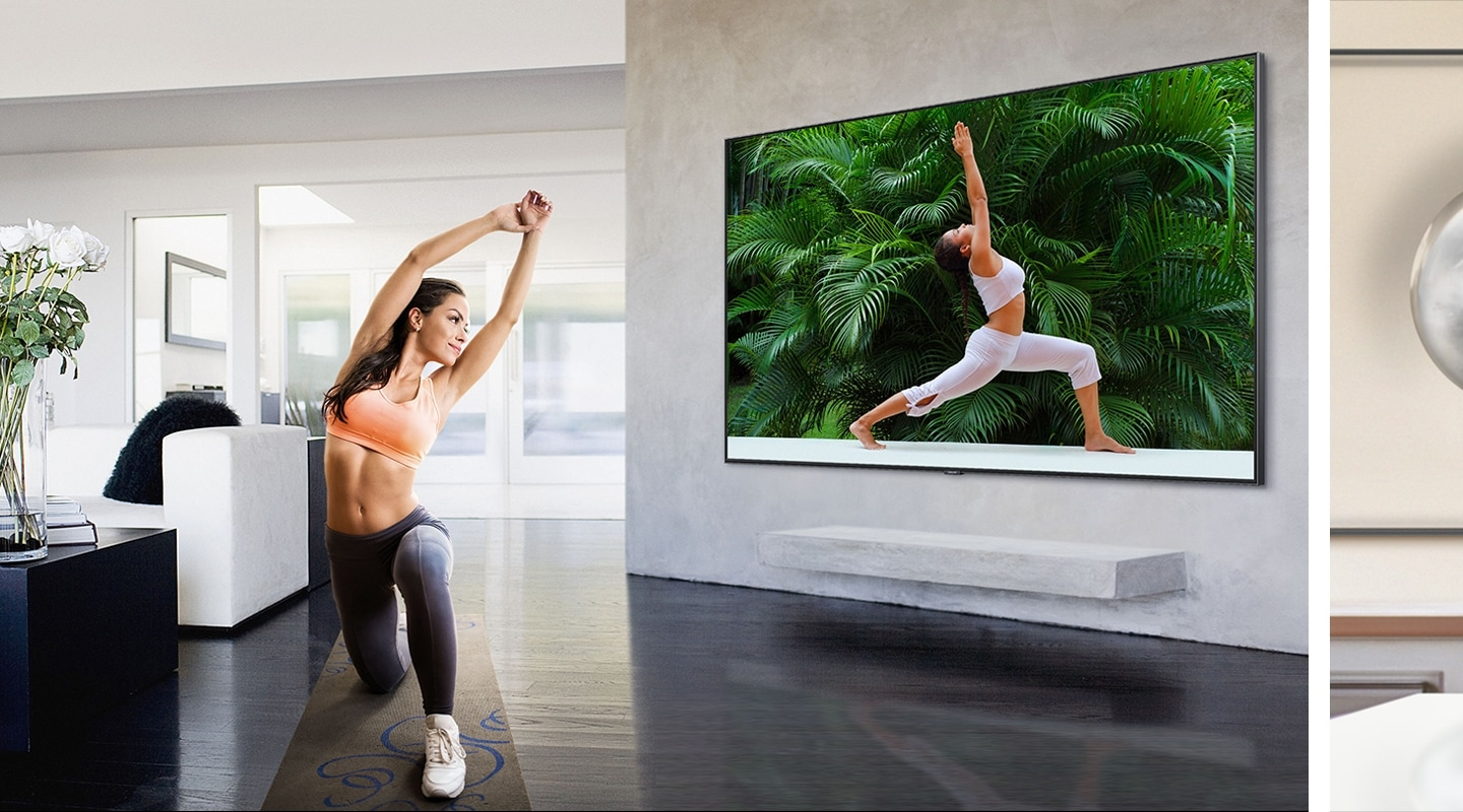 In a living room with white simple interior, a woman wearing a sportswear follows a yoga posture while watching a yoga training program on Super Big TV screen.