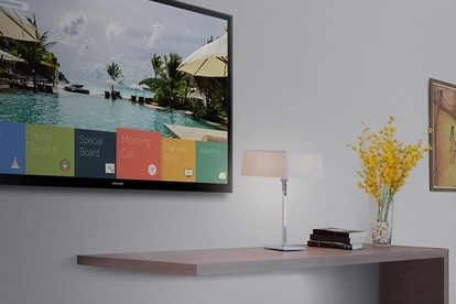 A Samsung Smart Signage TV showing customized content options in a hotel room