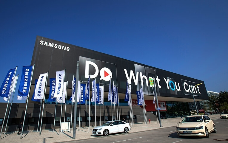 "Building exterior bearing the Samsung logo in the upper left corner and the slogan ""Do What You Can't"" with a row of Samsung logo banners placed in front of the building."