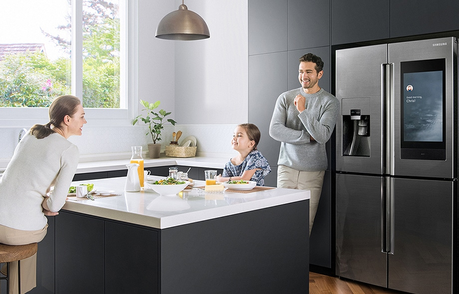 "A mother and daughter eat salad with orange juice in the kitchen, while the father watches over them and smiles while standing next to the Family Hub, where the screen display indicates rainy weather and reads ""Good Morning Chris."""