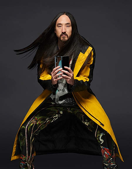 Steve Aoki standing with his knees slightly bent outward while sporting a yellow long coat as he holds up an unfolded Samsung Galaxy Fold smartphone.