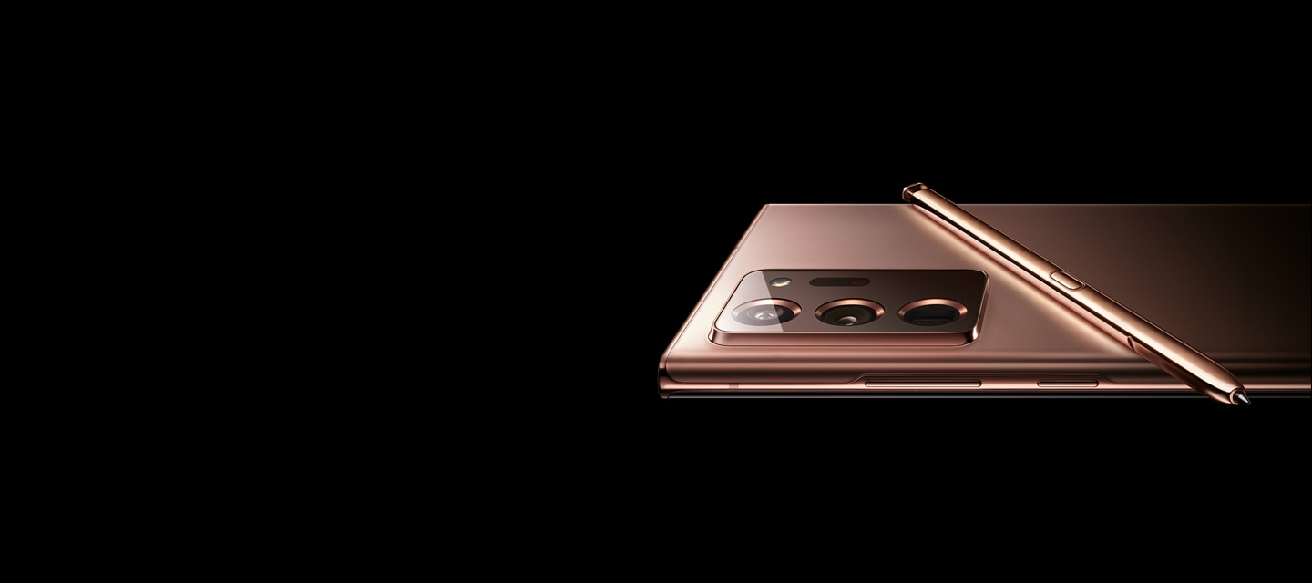 The upper half of Galaxy Note20 Ultra in Mystic Bronze, seen laying facedown in landscape mode. The matching S Pen is laying across its back.
