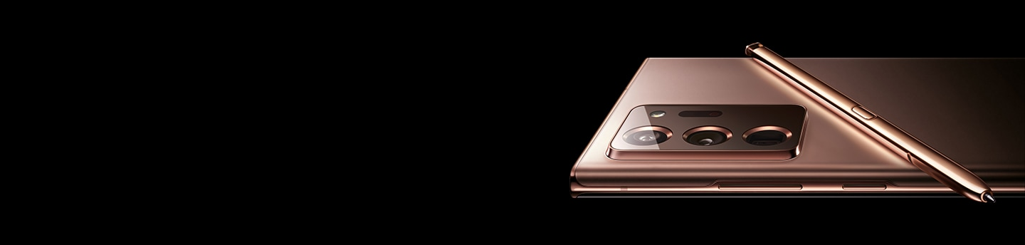 The upper half of Galaxy Note20 Ultra 5G in Mystic Bronze, seen laying facedown in landscape mode. The matching S Pen is laying across its back.