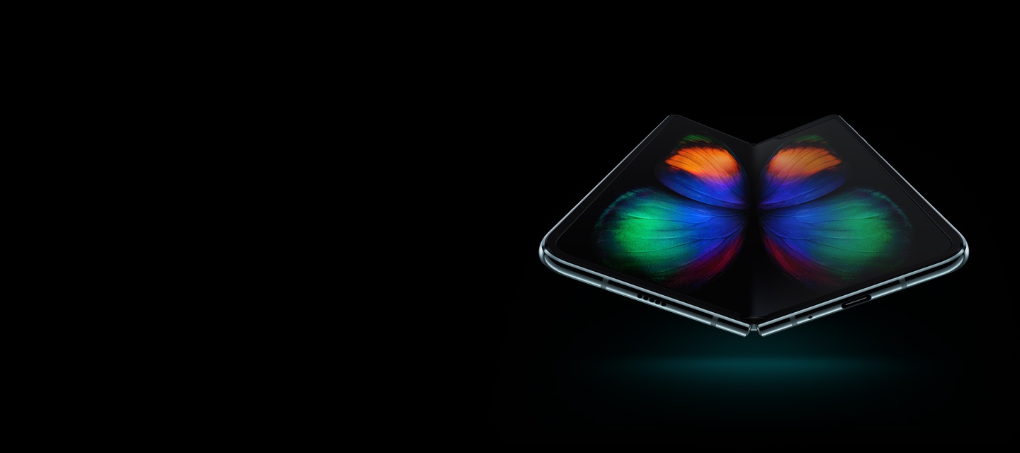 Galaxy Fold in Space Silver seen at a slight angle from the bottom, unfolded, with a multicolor butterfly graphic on-screen.