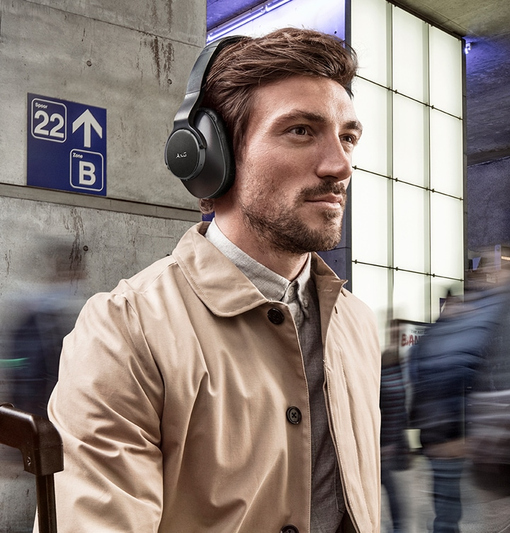 A man walking through a train station, wearing AKG N700NC M2 Wireless Headphones in black