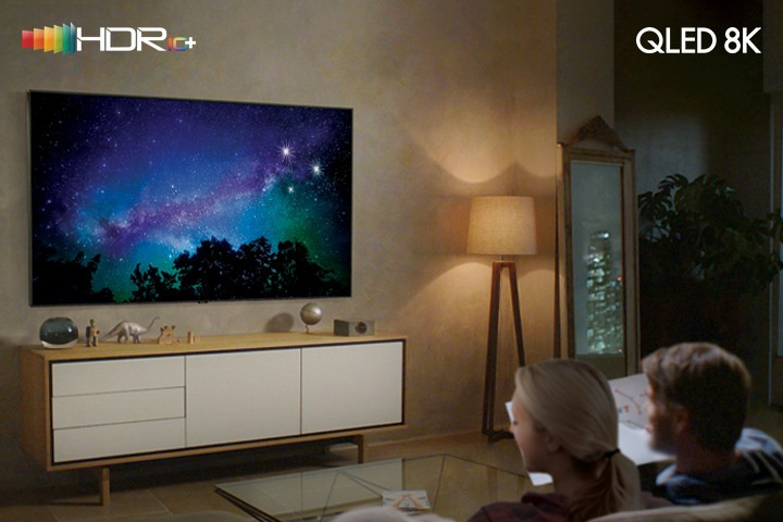 A son and father are taking a rest at home in front of the tv. There are the HDR10+ logo in the upper left corner and the QLED 8K logo in the upper right corner.