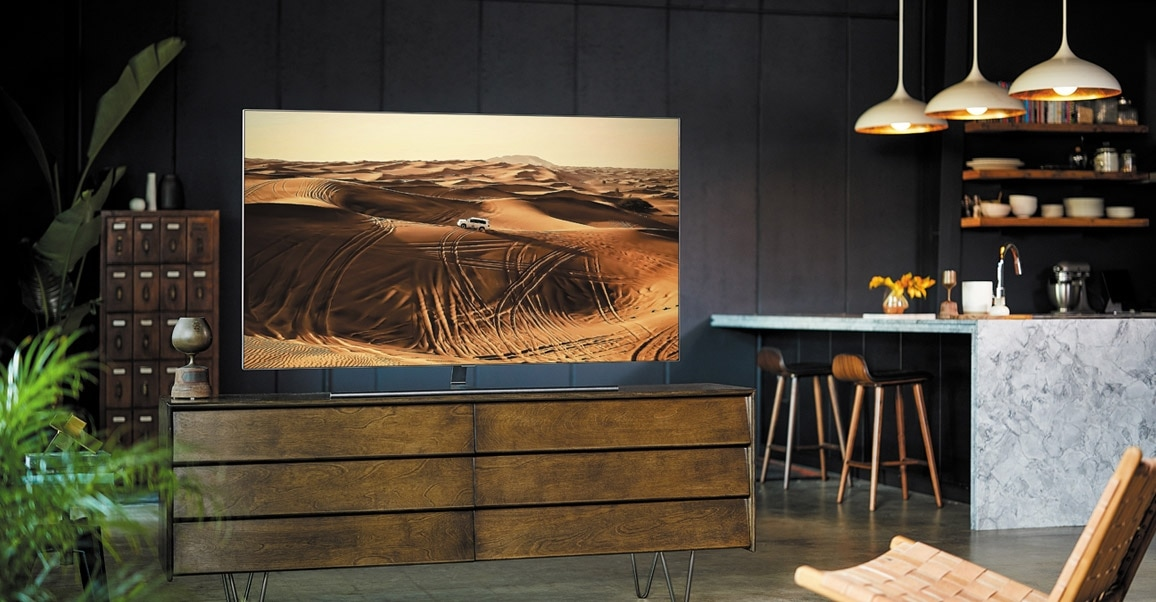 A lifestyle image of the 2018 new QLED TV Q7F.  Image shows QLED TV put in the wooden and dark  table.