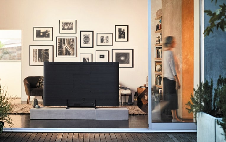 A lifestyle image of the 2018 new QLED TV Q9F.  Image shows back angle of the product put in the living room, and woman is just passing by.