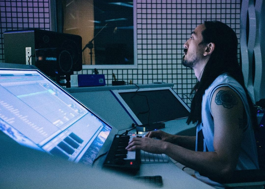 Steve Aoki playing on his keyboard while facing straight ahead, in the process of producing new music from his dimly-lit studio, the Neon Future Cave