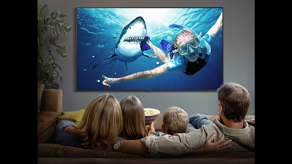 4 people are watching a spectacle movie on Super Big TV. On the screen, a woman wearing a swim suit is scuba diving and a shark is following her.
