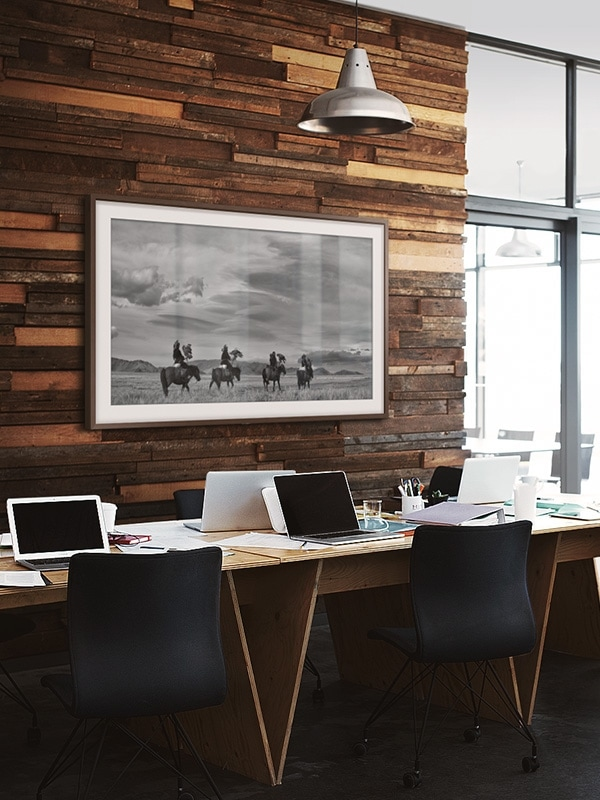 Image of an office with The Frame on the wall above a desk and chair.