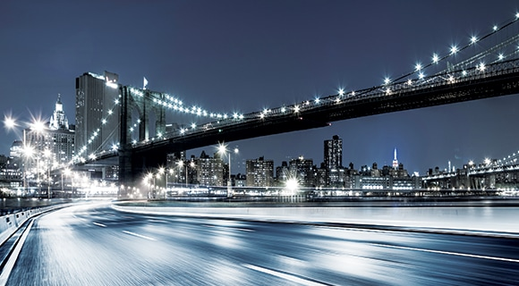 Samsung LEDs an empty high way with white lights shining along it and a suspension bridge lighted up across it