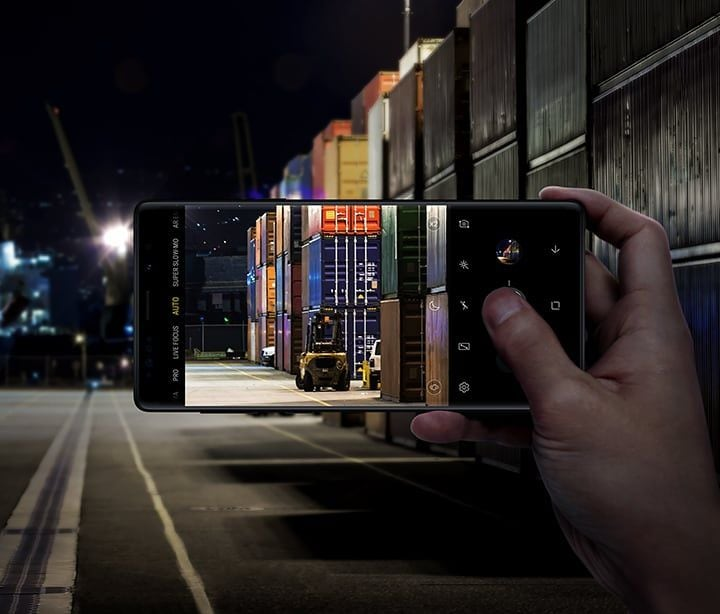 Image of person holding Galaxy Note9 and taking a photo of shipping containers in a warehouse, demonstrating Scene Optimizer