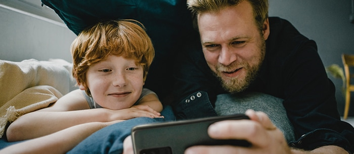 Father and son lay in bed on their bellies as the father holds a dark grey smartphone in landscape mode. Both the father and son smile as they gaze into the phone's display as if they're watching a show at home.