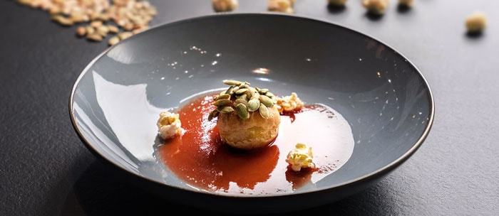 A round, glazed ceramic coupe of grey-blue carefully holds a layer of tomato coulis at the center, over which stands tall, a choux pastry hatted with caramel and seeds. The plate is perfected by a garnish of three popped corn kernels around the choux.