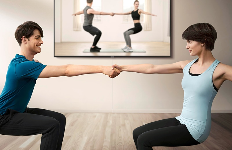 Couple gets ready to exercise in front of a big screen TV